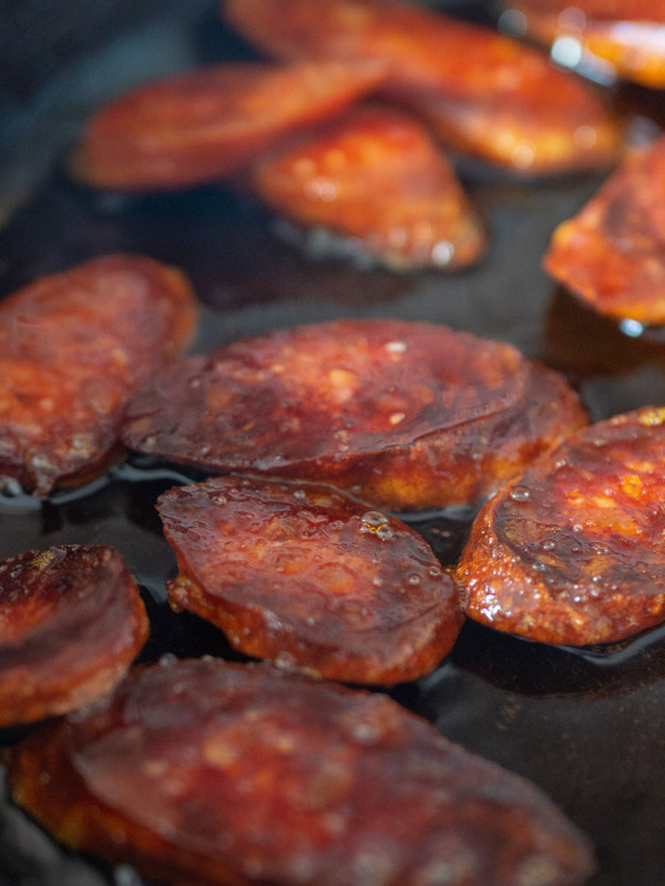chorizo cooking in a cast iron frying pan