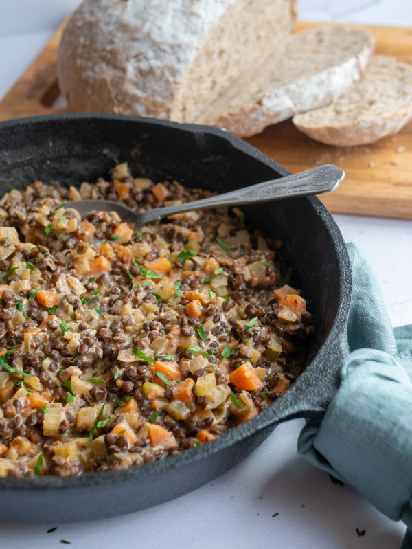 mustard lentil stew in a cast iron frying pan with a loaf of bread
