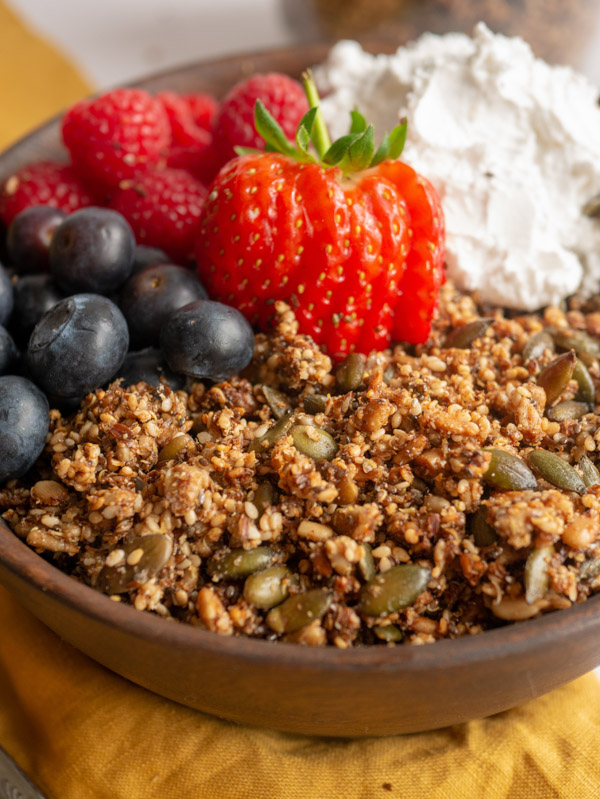quinoa seed granola in a bowl with berries and yoghurt