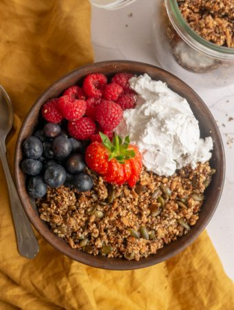 quinoa seed granola in a bowl with berries and yoghurt and a spoon