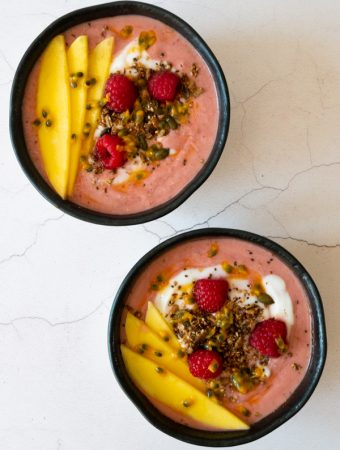 mango raspberry smoothie bowl topped with fresh mango, raspberries granola and passion fruit
