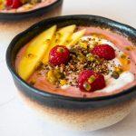 mango raspberry smoothie bowl topped with fresh mango, raspberries granola and passion fruit