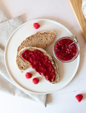 two slices of bread, one with raspberry flax jam on and a jar of raspberry flax jam on a plate