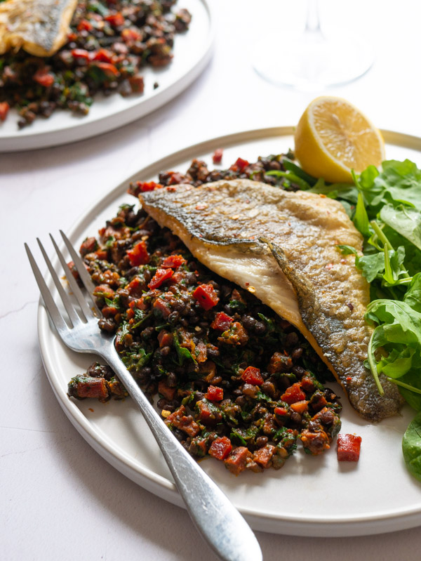 Pan-fried Sea Bass sits on top of Chorizo and Lentils with a side salad - all on a white plate with a fork.