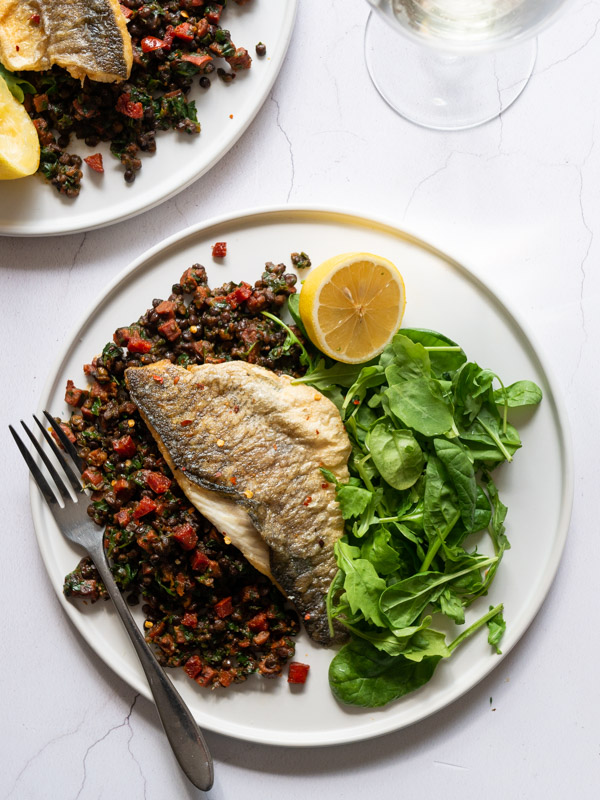 Sea Bass with Chorizo and Lentils and salad on a plate with a fork and a glass on wine
