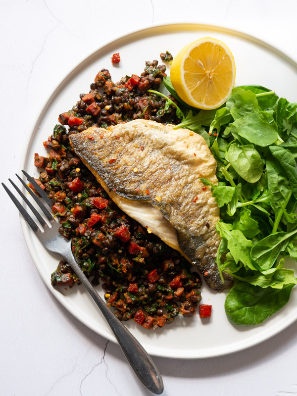 Pan-fried Sea Bass sits on top of Chorizo and Lentils with a side salad - all on a white plate with a fork. A glass of wine sits next to the plate.