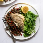 Sea Bass with Chorizo and Lentils and salad on a plate with a fork