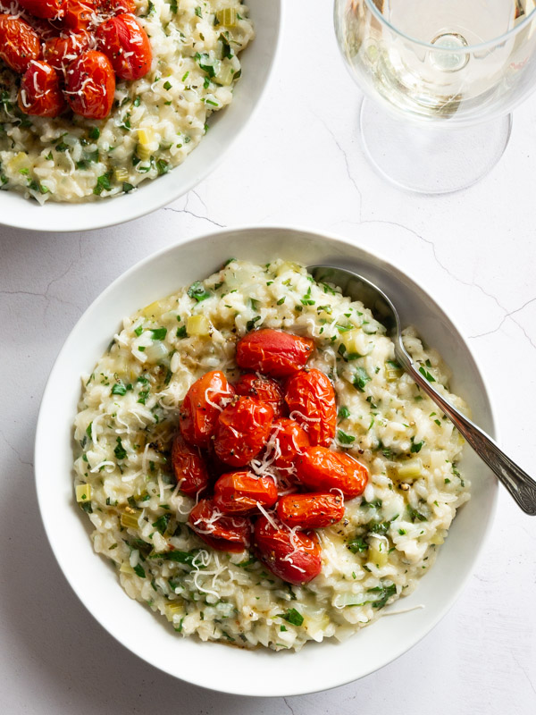 Herby Tabbouleh Risotto with Roast Tomatoes in a bowl with a spoon and a glass of white wine