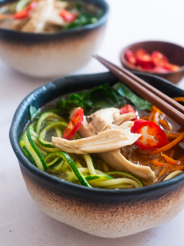 two bowls of Asian Chicken and Vegetable Noodle Soup with chopsticks