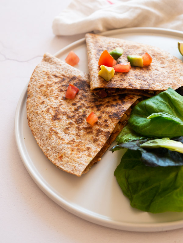 a quesadilla on a plate with salad