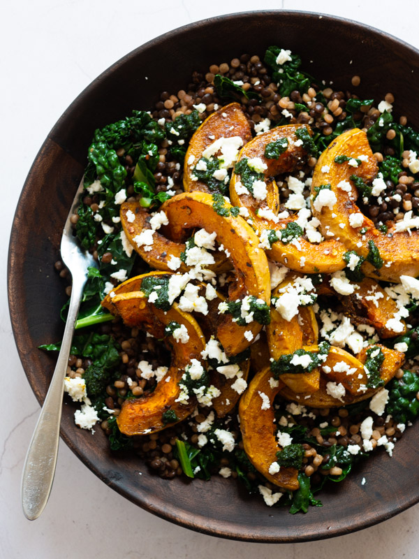 Roast Butternut Squash sitting on top of couscous, puy lentils and cavelo nero in a wooden bowl with a fork. On top of the squash is crumbled feta and raisin pesto.