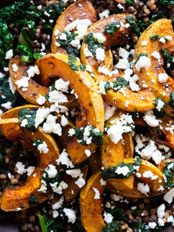 A close up of roast butternut squash, with crumbled feta and raisin pesto on top.