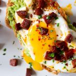 Chorizo, Avocado and Egg Toast on a white plate with a runny yolk