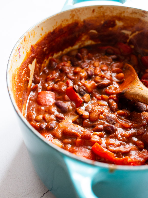 vegan chilli sin carne in a blue le cruset casserole dish with a wooden spoon