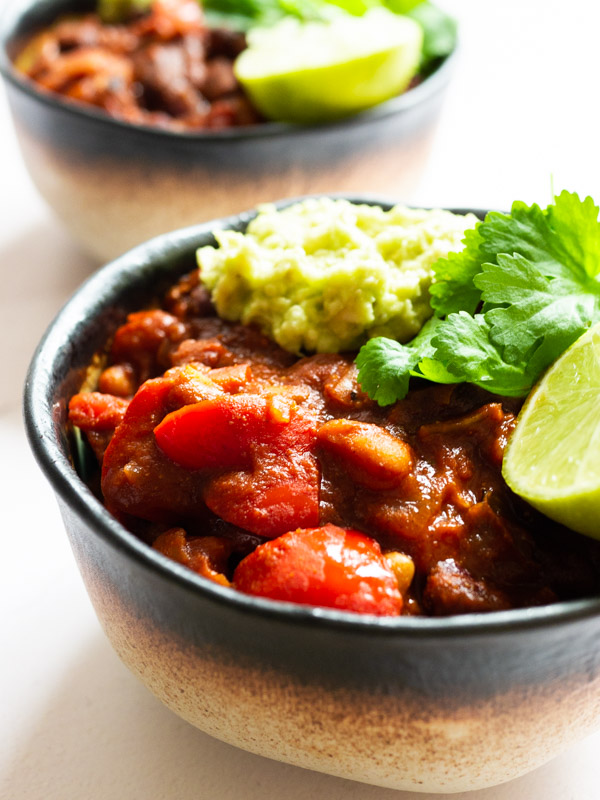 vegan chilli sin carne in an earthenware bowl, topped with guacamole, lime and coriander