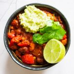 vegan bean chilli in a bowl with guacamole, lime and coriander