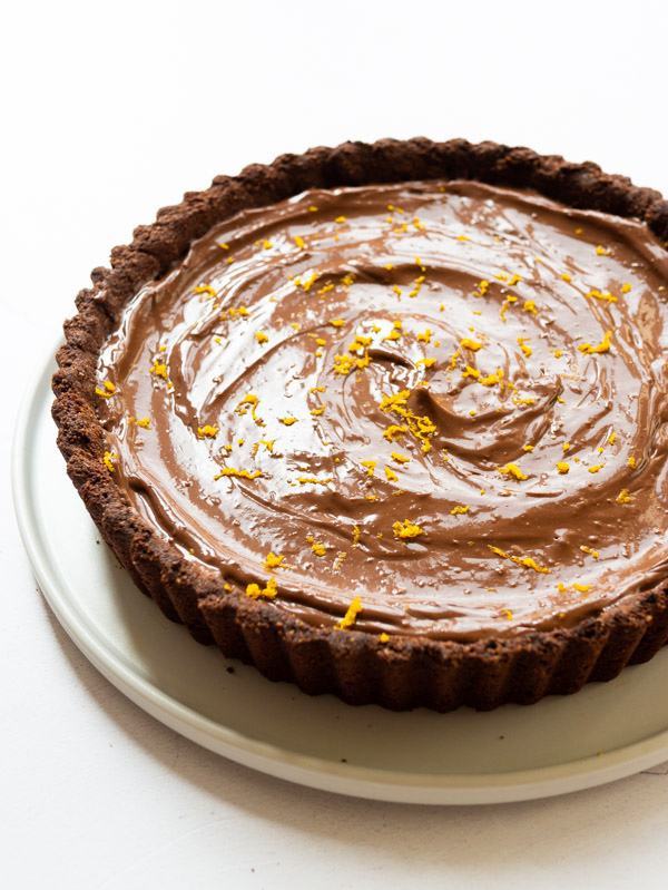 Vegan Chocolate Orange Tart on a plate with orange zest sprinkled on top.