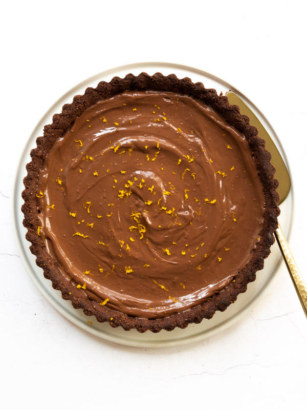 Vegan Chocolate Orange Tart on a plate with a cake slice
