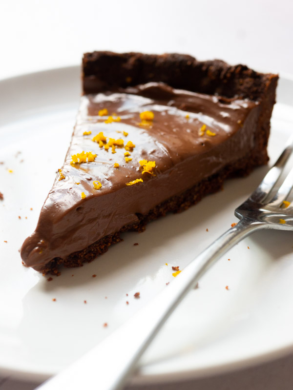 A slice of Vegan Chocolate Orange Tart on a plate with a fork. Orange zest is sprinkled on top of the tart.