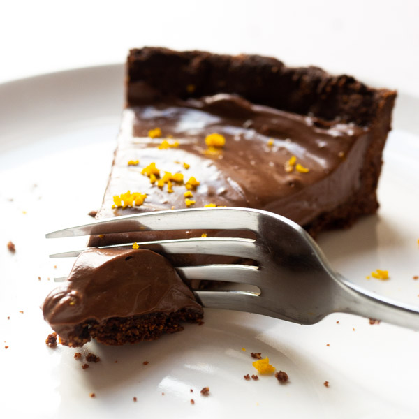 A slice of Vegan Chocolate Orange Tart being cut with a fork. Orange zest is sprinkled on top of the tart.