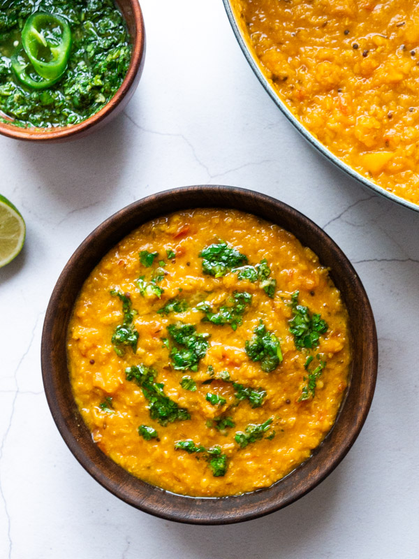 simple tadka dal with butternut squash in a wooden bowl, with coriander chutney drizzled on top.