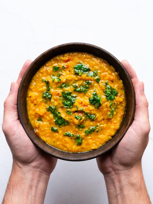 simple tadka dal with butternut squash in a bowl being held by two hands