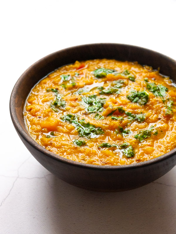butternut squash tadka dal in a wooden bowl with a drizzle of coriander chutney on top.