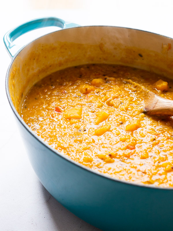 tadka dal with butternut squash in a teal le cruset cast iron casserole pot with a wooden spoon.