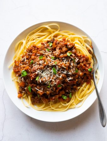 Mushroom and Lentil Spaghetti Bolognese in a white bowl with fork
