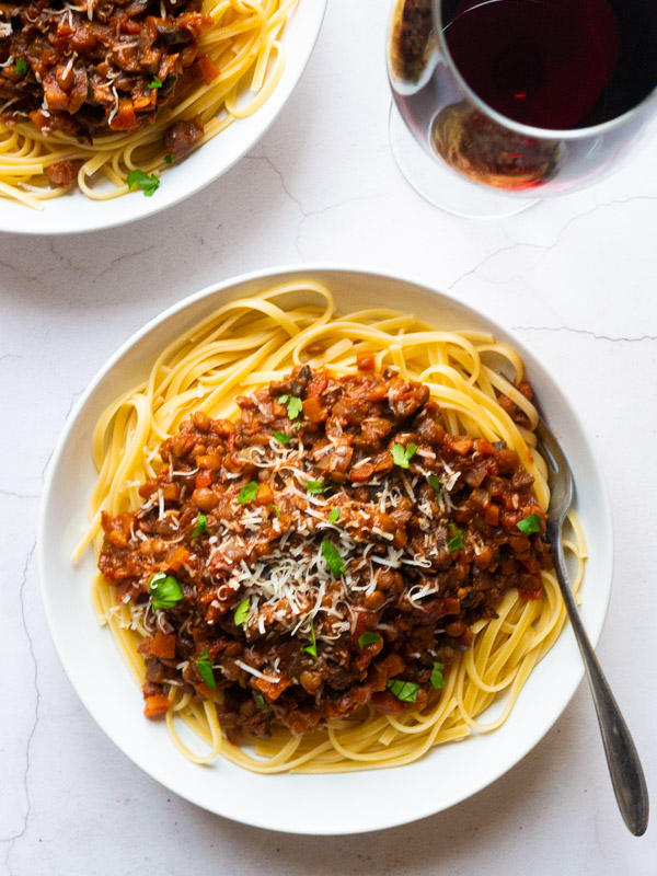 Vegan bolognese sauce on top of spaghetti, in a white bowl with a fork. A glass of red wine sits to the side of the bowl.