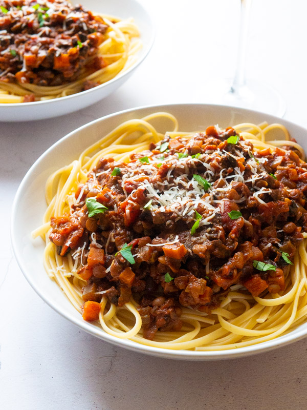 Vegan bolognese sauce on top of spaghetti, in a white bowl. A second bowl of the bolognese sauce is in the background, slightly out of focus.