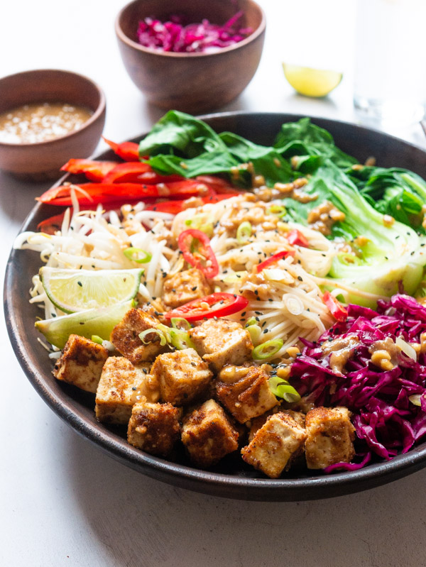 A wooden bowl filled with peanut tofu, noodles, pickled red cabbage, beansprouts, red pepper and bok choi then drizzled with peanut sauce. A bowl of peanut sauce and pickled cabbage is behind the bowl, slightly out of focus.