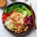 A peanut tofu noodle bowl with a small bowl of quick pickled red cabbage and peanut sauce