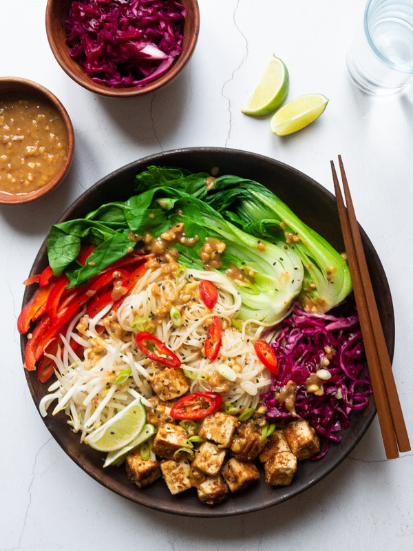 A wooden bowl filled with peanut tofu, noodles, pickled red cabbage, beansprouts, red pepper and bok choi then drizzled with peanut sauce. Chopsticks rest on the side of the bowl. A bowl of peanut sauce and pickled cabbage is next to the bowl.