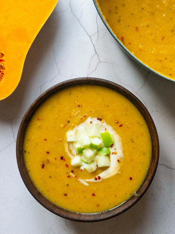 Spiced Squash, Celeriac and Apple Soup in a wooden bowl. The soup is garnished with a swirl of yoghurt, diced apple, and a sprinkle of chilli flakes.