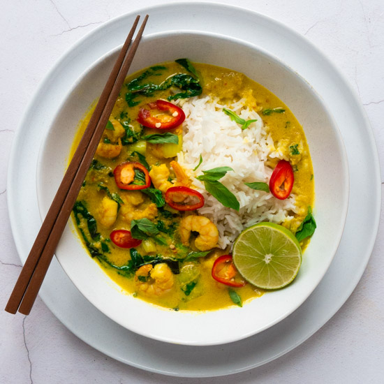 Cambodian Amok Prawn Curry served with rice in a white bowl, with chopsticks