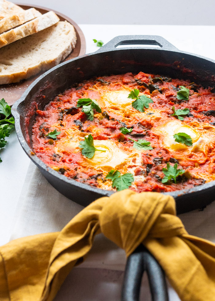 Shakshuka recipe with chorizo and kale in a cast iron frying pan. A yellow napkin is tied around the handle. Slices of bread on a wooden board can be seen in the background.