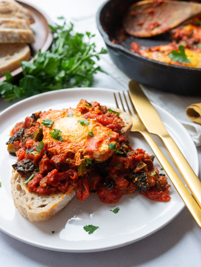A portion of shakshuka with chorizo and kale is served on top of a slice of bread on a white plate with a knife and fork alongside it. In the background there is the cast iron frying pan that the shakshuka was cook in and a wooden board with slices of bread and a bunch of parsley.