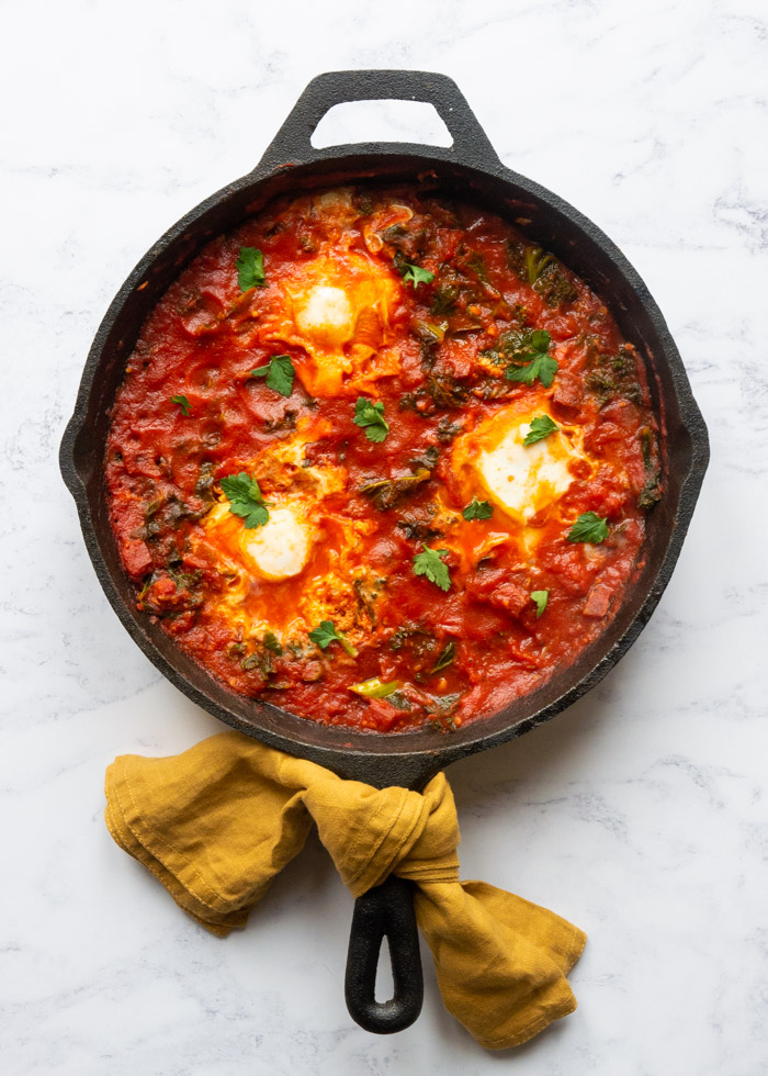 Shakshuka recipe with chorizo and kale in a cast iron frying pan sitting on top of a marble background. A yellow napkin is tied around the handle of the pan.