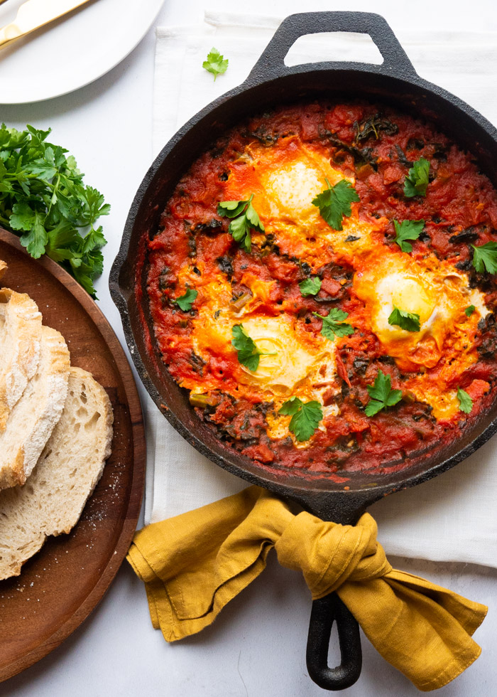 Shakshuka recipe with chorizo and kale in a cast iron frying pan. A yellow napkin is tied to the handle. Alongside the pan is a wooden board with slices of bread and a bunch of parsley.