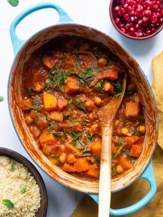Moroccan Vegetable Tagine in a Le Cruset Pot with a wooden spoon. A bowl of couscous to one side of the pot and a smaller bowl of pomegranate seeds to the other side.