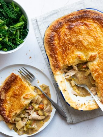 On overhead picture of Vegetable, Chicken and Bacon Pie in an enamel baking dish. One slice has been removed and sits on a white plate with a fork. A bowl of cooked savoy cabbage is placed next to the plate.