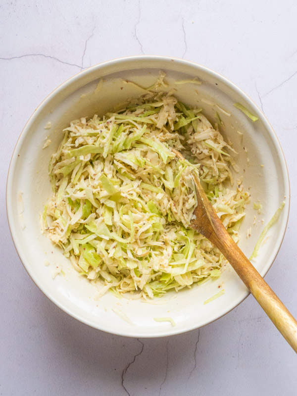 Parsnip, Cabbage and Celeriac Remoulade in a bowl with a wooden spoon - suggesting it has just been mixed together.