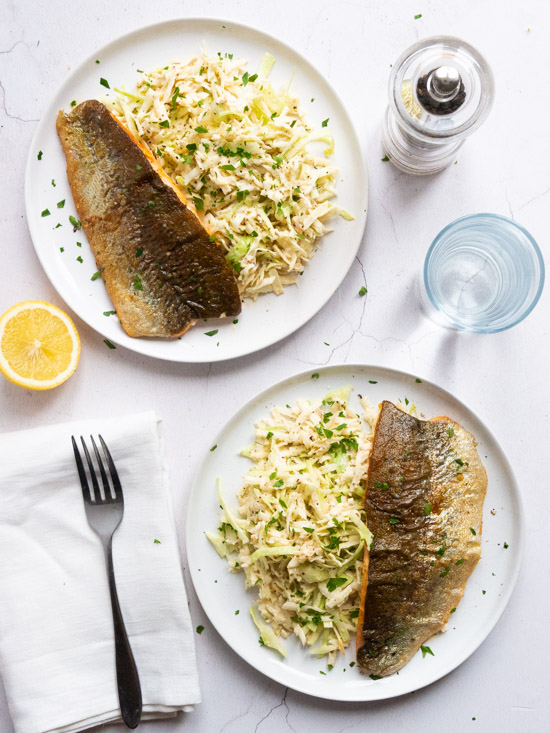 Two plates of Parsnip, Cabbage and Celeriac Remoulade with Pan Fried Trout Fillet, alongside a fork and napkin, a glass of water, a pepper grinder and a lemon wedge.