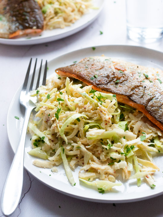 Parsnip, Cabbage and Celeriac Remoulade with Pan Fried Trout Fillet on a plate with a fork. A second plate can be seen in the background.