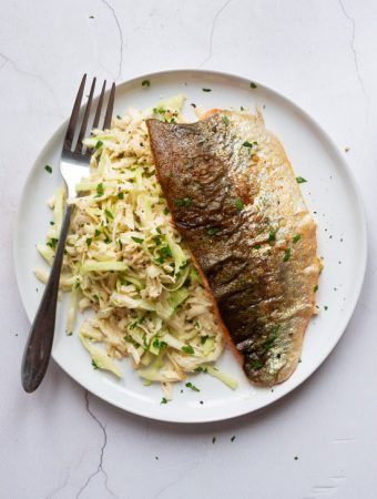 Parsnip, Cabbage and Celeriac Remoulade with Pan Fried Trout Fillet on a white plate with a fork