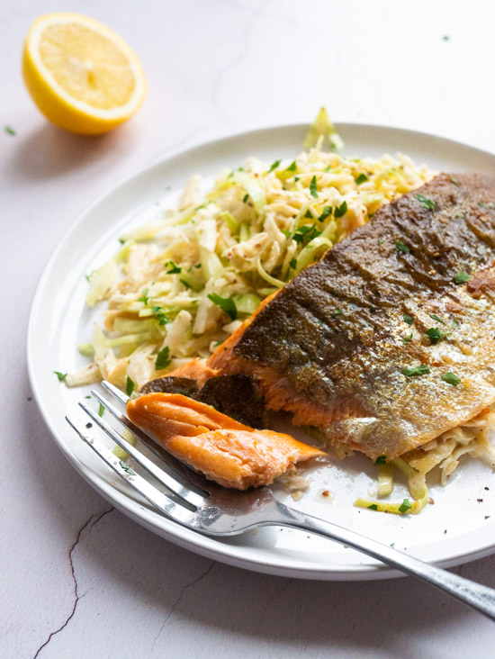 Parsnip, Cabbage and Celeriac Remoulade with Pan Fried Trout Fillet on a white plate. A piece of trout is broken off with a fork. There is a lemon wedge in the background.
