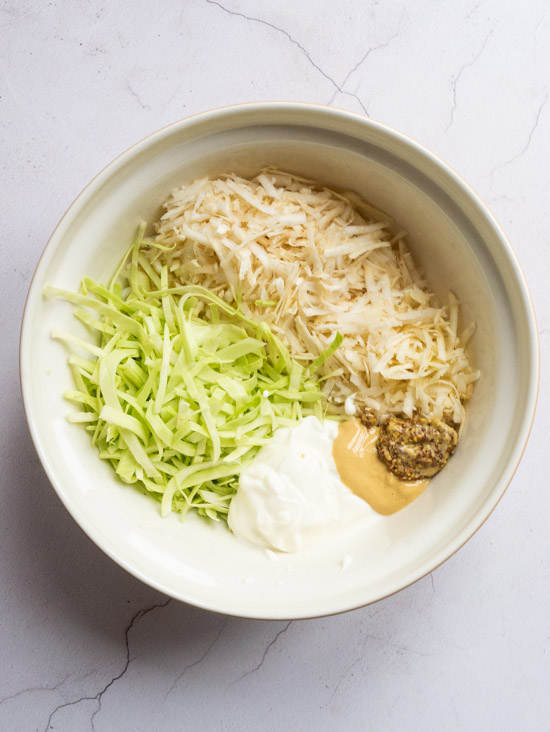 A bowl of parsip, cabbage and celeriac with yoghurt and mustard, ready to be mixed together to make Parsnip, Cabbage and Celeriac Remoulade