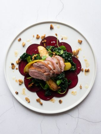 Winter Salad with Pan-Fried Duck Breast on a white plate with honeyed walnuts sprinkled on top.