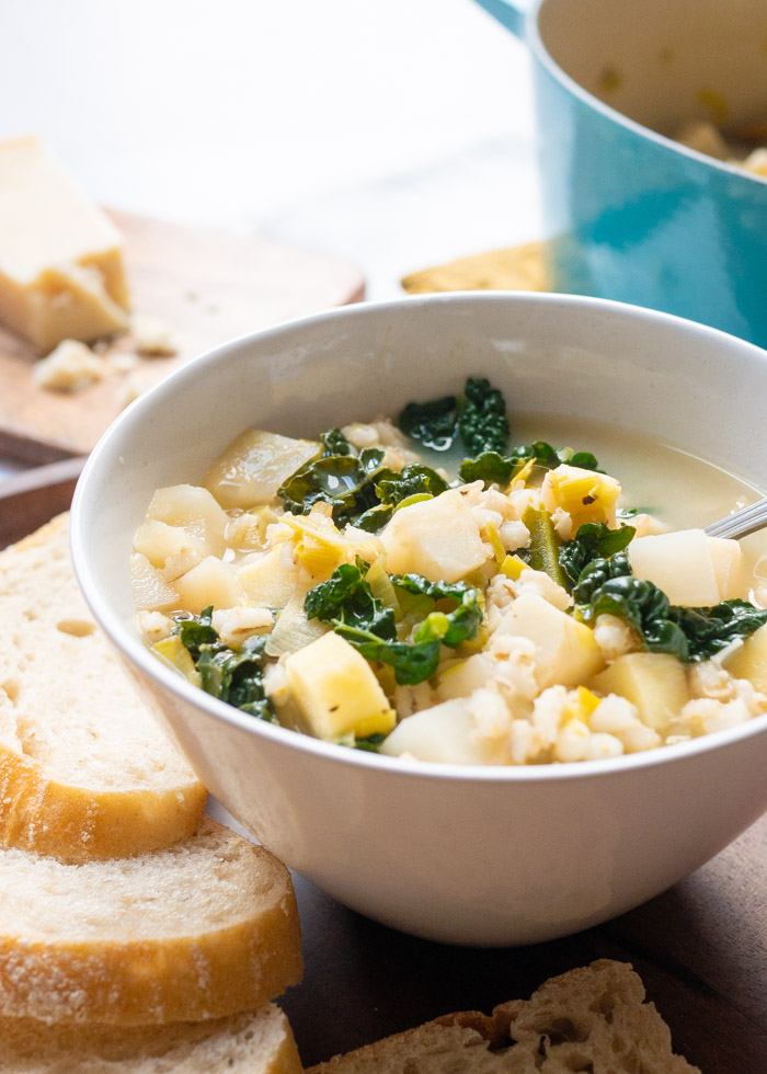 A bowl of Winter Vegetable Soup with Barley and Parmesan with slices of bread next to it. In the background there is a blue le cruset pot and a board with a wedge of parmesan.